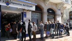 Una fila de personas espera para comprar la Lotería del Niño.